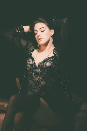 Sensuele jonge vrouw dragen zwarte kant lingerie zittend op een stoel in de slaapkamer terwijl haar Haar naar achteren en de ogen zijn gesloten.