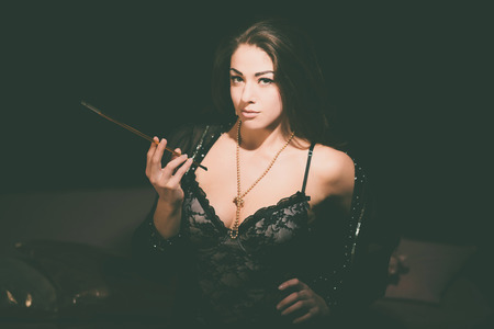 Seductive Young Woman Wearing Black Lingerie Fashion Holding a Long Cigarette Pipe While Looking at the Camera on a Black Background.