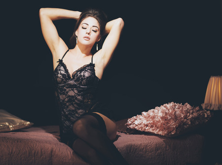 Gorgeous Young Woman Wearing Sexy Black Lingerie Sitting on a Pink Bed Sensually with Both Arms Raised and Eyes Closed.