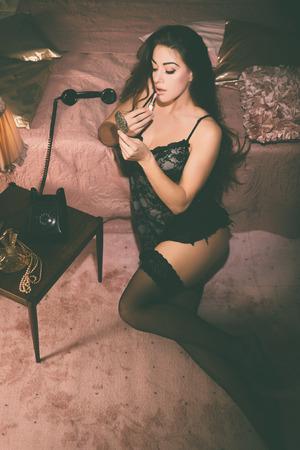 prostituta: Seductora mujer joven en un elegante Negro Lencería inclinada sobre su cama rosa, mientras que poner lápiz labial del maquillaje. Capturado en Vista elevada.
