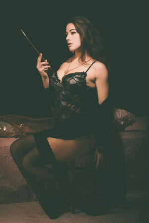sensually: Sexy Young Woman in Black Lace Lingerie Holding a Smoking Pipe While Sitting on a Chair and Looking to the Left of the Frame Sensually.