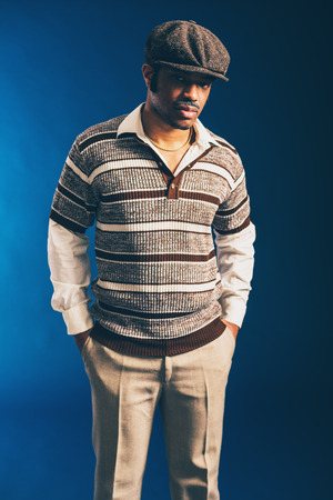 introspective: Close up Portrait of an Afro Man in Trendy Attire, Wearing Long Sleeved Shirt and Cap, Standing with Hands in the Pocket and Looking at the Camera on a Dark Blue Background. Stock Photo