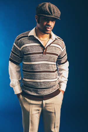 sombre: Close up Portrait of a Stylish Afro Man Wearing Brown Striped Shirt and Flat Cap, Looking at the Camera Seriously on a Dark Blue Background. Stock Photo