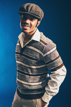 dapper: Close up Portrait of a Smiling Afro Man in Trendy Fashion, Wearing Long Sleeved Shirt and Cap, Looking at the Camera with Hands in the Pocket. Captured in Studio with a Dark Blue Background.