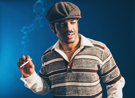eyes downcast: Close up Portrait of a Fashionable Young Afro Man, Wearing Striped Shirt and Cap, Smoking a Cigarette while Looking to the Right of the Frame. Captured in Studio with a Dark Blue Background.