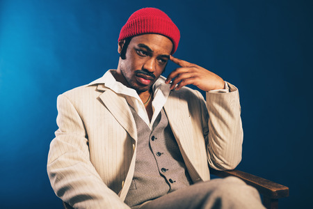 reverie: Worried handsome African American man in a stylish suit and red cap sitting staring thoughtfully at the floor with a sombre expression