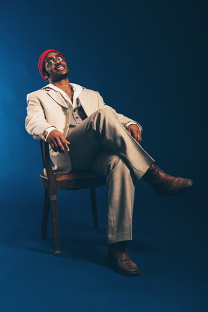 pleased: Happy contented African American man sitting unwinding in a wooden armchair leaning back with a pleased smile on his face, over blue