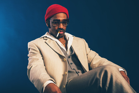 dangling: Worried stylish attractive Afro-American businessman with a cigarette dangling from the side of his mouth sitting in an armchair staring at the floor