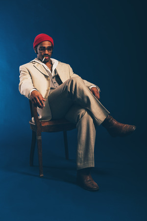 unwinding: Stylish attractive African American businessman sitting smoking in a chair with a cigarette dangling from his mouth staring absentmindedly at the floor, on blue