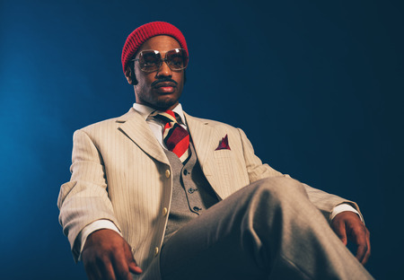 inscrutable: Close up Portrait of a Pensive Young Afro Man in Formal Wear with Red Cap and Sunglasses Sitting on a Chair and Looking Afar. Captured in Studio with a Dark Blue Background. Stock Photo