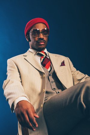 impassive: Close up Portrait of a Serious Young Afro Man in Formal Wear with Red Cap and Sunglasses Napping on a Chair. Captured in Studio with a Dark Blue Background. Stock Photo