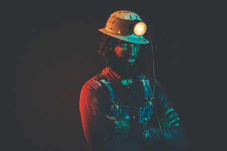 hairy arms: Portrait of Angry Looking Male Miner Wearing Lit Safety Helmet Lamp and Standing with Arms Crossed Illuminated with Blue Light Stock Photo