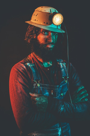hairy arms: Portrait of Stern Looking Bearded Male Miner Wearing Safety Helmet Lamp with Arms Crossed Illuminated with Blue Light and Copy Space to the Side Stock Photo