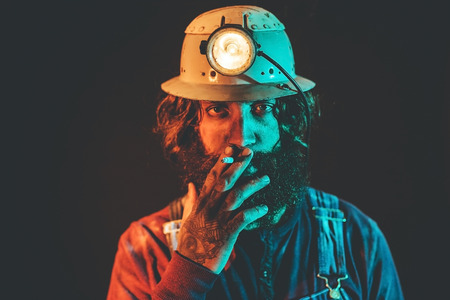 shadowy: Miner with long curly hair and a bushy beard wearing hardhat with shining lamp taking a cigarette break, dark shadowy portrait
