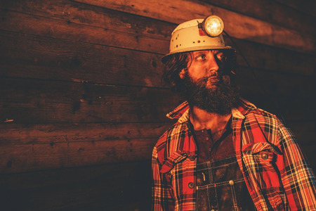 Close Up of Male Miner Wearing Lit Safety Helmet Lamp and Plaid Shirt Leaning Against Wooden Wall and Looking to the Side in Warm Yellow Light 스톡 콘텐츠