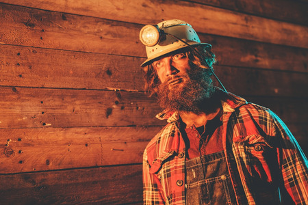 unemotional: Male Miner Wearing Lit Safety Helmet Lamp Leaning Against Wooden Wall in Plaid Shirt and Looking into the Distance