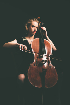 recital: Attractive young woman playing the cello in the darkness at a recital or classical concert, full length portrait Stock Photo