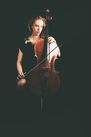 cellist: Portrait of a Pensive Lady Cellist Holding a Cello Instrument While Looking to the Right Seriously on a Black Background.