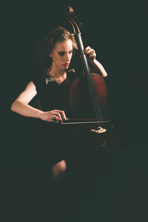 recital: Pretty young woman playing a cello at night during a concert or classical recital sitting in her chair with the instrument in front of her