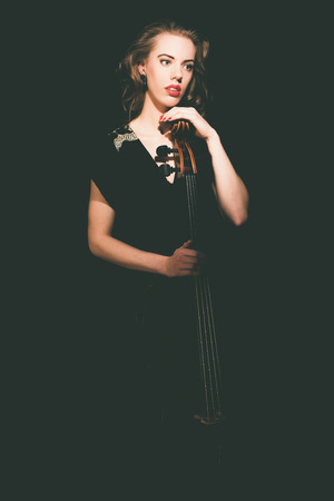 recital: Elegant young female cellist waiting with her cello in the darkness for the start of a concert or recital at the academy