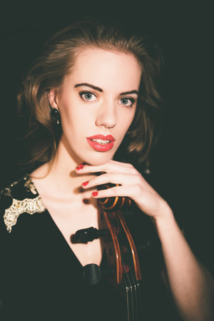 wide eyed: Pretty stylish young classical cellist sitting in the darkness holding the top of her cello looking at the camera with a serious wide eyed expression Stock Photo