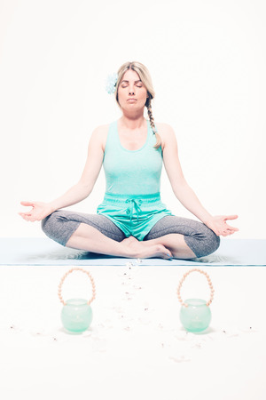 seeks: Relaxed attractive young blond woman sitting barefoot in the lotus position meditating with her eyes closed as she seeks spiritual enlightenment
