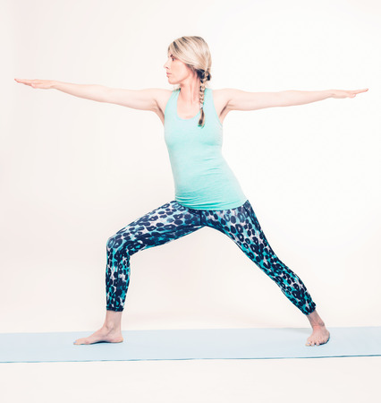 virabhadrasana: Active Young Blond Woman in Virabhadrasana II or Warrior 2 Pose While Doing Yoga Exercise on a Mat. Isolated on White.