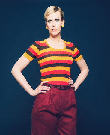 short pants: Portrait of a Pretty Blond Woman Posing in Casual Striped Shirt and Short Pants with Hands on Waist, Isolated on Dark Blue Background. Stock Photo
