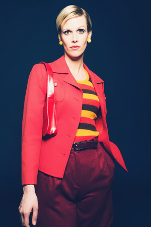 svelte: Portrait of a Stylish Blond Woman in Red and Yellow Fashion, Wearing Striped Shirt, Red Blazer and Shorts with Shoulder Bag, Looking at the Camera. Isolated on Dark Blue.