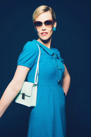 Stylish short haired blond woman in sunglasses and a blue summer dress wearing a white handbag over her shoulder as she poses for the camera Stock Photo