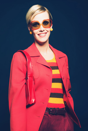 modish: Smiling friendly woman in trendy summer fashion wearing a stylish colorful red and yellow striped outfit and jacket with modern sunglasses and handbag, studio portrait