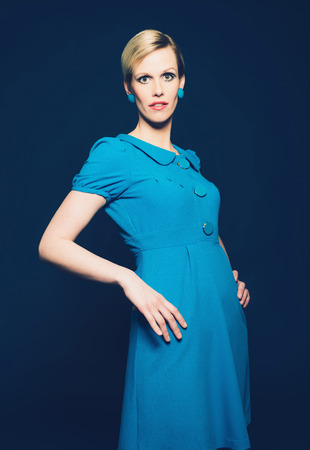 Portrait of a Stylish Blond Lady Posing in Elegant Plain Blue Dress and Earrings with Hands on Hips, Looking at the Camera on Dark Blue Background. Imagens