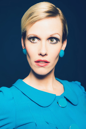 elfin: Serious mature blond woman with an elfin face and serious expression wearing a stylish blue dress and earrings Stock Photo