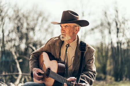 sombre: Lonely country and Western musician sitting outdoors in woodland strumming his guitar and staring into the distance with a sombre expression