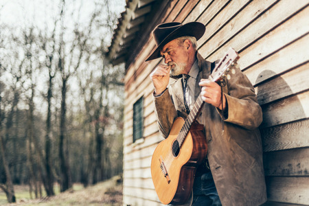 senior smoking: Senior Country and Western Male Musician with Guitar Instrument, Smoking a Cigarette While Leaning on the Wooden Wall of his House.
