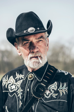 senior smoking: Handsome senior bearded American man in a black country and Western outfit standing outdoors in the sunshine smoking a cigarette Stock Photo