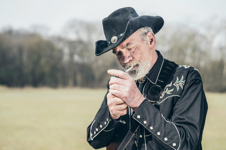 stetson: Senior stylish man in a black Western outfit and stetson lighting up a cigarette as he stands outdoors in the sunshine