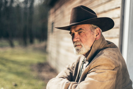 unwind: Close up Pensive Senior Western Man, Wearing Jacket and Cowboy Hat, Sitting on Steps in Front of his House and Looking Afar Seriously. Stock Photo