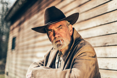 observant: Close up Smoking Elderly Western Man Looking Afar Seriously While Unwinding In Front of his House. Stock Photo