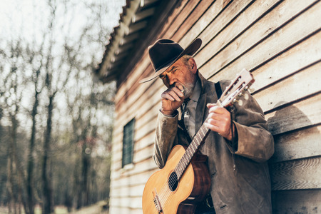 senior smoking: Smoking Senior Country-Western Male Guitarist Holding his Guitar While Leaning on the Wall of his House and Looking at the Camera.