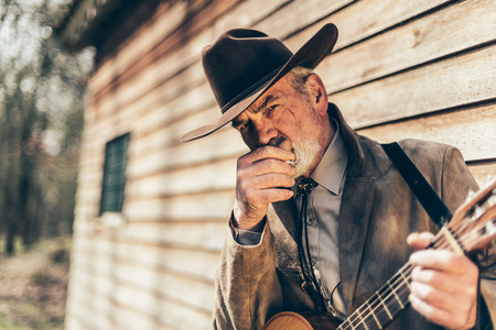 stetson: Thoughtful grey-haired country musician in a stetson standing holding his guitar in front of a log cabin looking at the camera