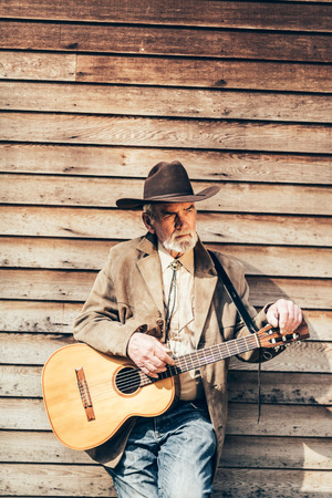 cowboy beard: Senior bearded male guitarist taking a break relaxing leaning against a rustic wooden cabin with his guitar around his neck looking off thoughtfully to the side