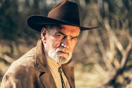 penetrating: Serious senior man with a grey beard wearing a wide brimmed stetson sitting outdoors in the countryside giving the camera a penetrating stare