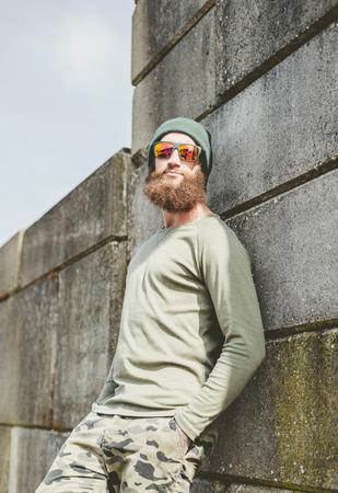 jaunty: Relajado hombre joven con una gran barba espesa apoyado contra una pared alta de piedra en la gorra y gafas de sol disfrutando del sol, vista de �ngulo bajo