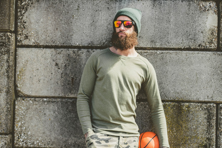 mates: Athletic bearded young man with a basketball standing waiting in his cap and t-shirt leaning against a high wall as he waits for his team mates Stock Photo