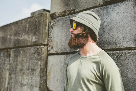 casual attire: Close up Thoughtful Young Man in Casual Attire with Unshaven Beard Leaning on Concrete Wall and Looking to Far Left. Stock Photo