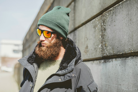 bonnet up: Close up Pensive Young Man with Unshaven Beard, Wearing Casual Jacket and Bonnet with Sunglasses, Looking to the Left While Standing Beside Old Street Wall.
