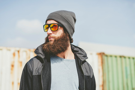 inscrutable: Man with a bushy beard wearing sunglasses standing in front of a row of metal containers looking to the left of the frame as though waiting for someone