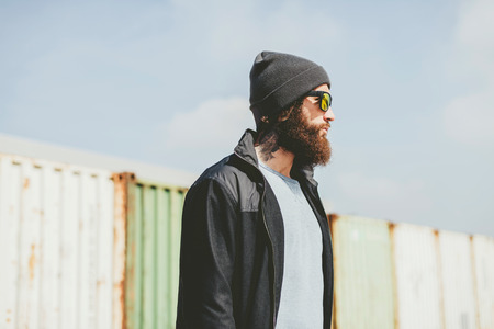 young unshaven: Young Man with Unshaven Beard, Wearing Casual Jacket with Bonnet and Sunglasses, Standing Near the Container Vans and Looking to the Right.