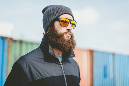 bonnet up: Close up Serious Young Man with Long Beard in Black Jacket and Bonnet with Sunglasses, Looking to Far Right Seriously.